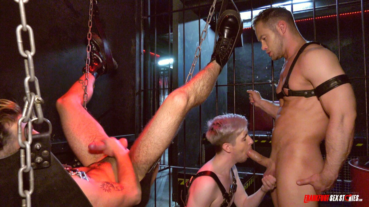 young blond stud sucks big cock next to a guy in a sling